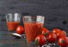 Dos vidrios de jugo de tomates fresco con la sal, tomates de cereza en fondo oscuro imagen de archivo libre de regalías