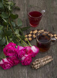 Dos vidrios de la bebida, de galletas y del ramo de rosas rojas del escarlata Fotos de archivo
