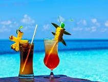 Dos vidrios de la bebida en una tabla de la playa Fotos de archivo