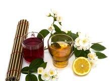 Dos vidrios de la bebida y del limón en un fondo blanco Foto de archivo