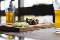 Dos, 2 vidrios de la cerveza, carne con las verduras en la tabla, comida Foto de archivo