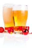 Dos vidrios de la cerveza, cinta roja y bolas de la Navidad Imágenes de archivo libres de regalías