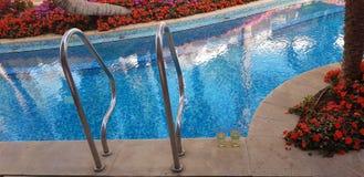 Dos vidrios de la vid blanca hacen una pausa la piscina foto de archivo