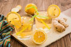 Dos vidrios de limonada con el jengibre y el limón en una tabla de madera Fotografía de archivo