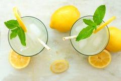 Dos vidrios de limonada con la menta, opinión de arriba sobre el mármol Fotos de archivo libres de regalías