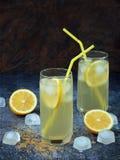 Dos vidrios de limonada hecha en casa fría con las rebanadas del limón, los cubos de hielo, el azúcar marrón y la paja Imagen de archivo