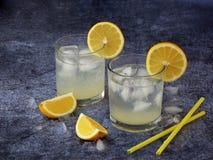Dos vidrios de limonada hecha en casa fría con las rebanadas del limón, los cubos de hielo y la paja en fondo oscuro Copie el esp Fotografía de archivo