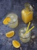 Dos vidrios de limonada hecha en casa fría con las rebanadas del limón, los cubos de hielo y la paja en fondo oscuro Copie el esp Fotos de archivo