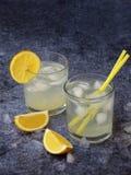 Dos vidrios de limonada hecha en casa fría con las rebanadas del limón, los cubos de hielo y la paja en fondo oscuro Copie el esp Imagen de archivo libre de regalías