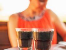 Dos vidrios de soda en la tabla y una mujer en el fondo fotografía de archivo libre de regalías