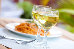 Dos vidrios de vino blanco con espagueti en tomate Imágenes de archivo libres de regalías