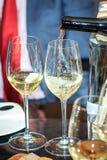Dos vidrios de vino blanco, el proceso de verter el vino Foto de archivo