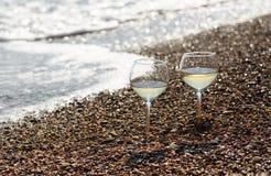 Dos vidrios de vino blanco en la playa Foto de archivo libre de regalías