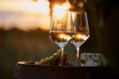 Dos vidrios de vino blanco en la puesta del sol Fotografía de archivo libre de regalías