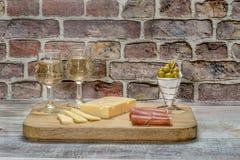 Dos vidrios de vino blanco en una tabla con el jamón, el queso y aceitunas Fotos de archivo libres de regalías