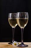 Dos vidrios de vino blanco en una tabla de madera Foto de archivo