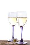 Dos vidrios de vino blanco en una tabla de madera con una manzanilla Imagen de archivo