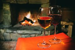 Dos vidrios de vino blanco rojo, fondo de la chimenea de la chimenea postal romántica de Navidad, interior acogedor de una tarde  fotos de archivo libres de regalías