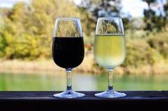 Dos vidrios de vino blanco rojo y en el carril de madera Fotos de archivo libres de regalías
