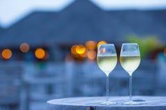 Dos vidrios de vino blanco sabroso en la puesta del sol imagenes de archivo