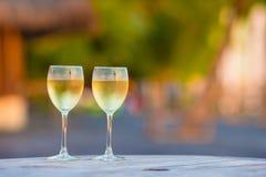 Dos vidrios de vino blanco sabroso en la puesta del sol Fotografía de archivo libre de regalías
