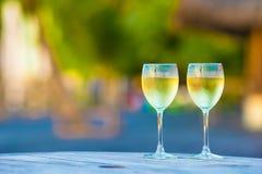 Dos vidrios de vino blanco sabroso en la puesta del sol encendido Fotografía de archivo libre de regalías