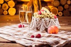 Dos vidrios de vino blanco y de las frutas jugosas en la cesta de mimbre imagenes de archivo