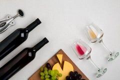 Dos vidrios de vino blanco y rojo, de queso y de las uvas Visión superior Imagen de archivo libre de regalías