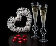Dos vidrios de vino con el corazón y los dulces Foto de archivo libre de regalías