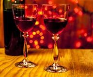 Dos vidrios de vino con las luces en el fondo Imágenes de archivo libres de regalías