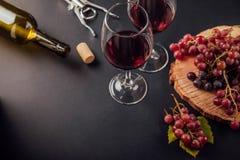 Dos vidrios de vino con una botella, un sacacorchos y uvas Fotografía de archivo