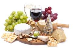 Dos vidrios de vino, de uvas, de queso y de galletas Fotos de archivo libres de regalías