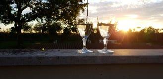 Dos vidrios de vino en puesta del sol imagen de archivo libre de regalías