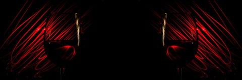 Dos vidrios de vino en un fondo rojo resumen rayas ligeras en un negro Foto de archivo libre de regalías