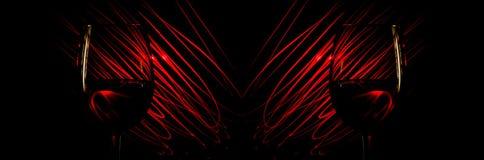 Dos vidrios de vino en un fondo rojo resumen rayas ligeras en un negro Fotografía de archivo libre de regalías