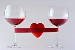 Dos vidrios de vino envueltos con la cinta y el corazón Imagenes de archivo