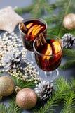 Dos vidrios de vino reflexionado sobre caliente con las especias y la naranja cortada Bebida de la Navidad con la vela y las deco foto de archivo libre de regalías