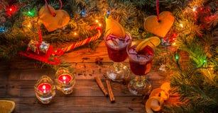 Dos vidrios de vino reflexionado sobre con las rebanadas, las velas y el árbol de navidad anaranjados con la guirnalda y los jugu Imágenes de archivo libres de regalías