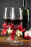 Dos vidrios de vino rojo con los ornamentos de la Navidad Imagen de archivo libre de regalías