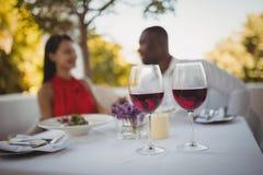 Dos vidrios de vino rojo con los pares en fondo Fotografía de archivo libre de regalías