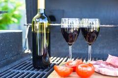 Dos vidrios de vino rojo, de filete y de tomates en barbacoa al aire libre Fotos de archivo