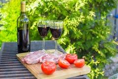 Dos vidrios de vino rojo, de filete y de tomates en barbacoa al aire libre Fotografía de archivo