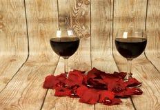 Dos vidrios de vino rojo, de pétalos color de rosa y de corazones de la tarjeta del día de San Valentín encendido cortejan Fotografía de archivo libre de regalías