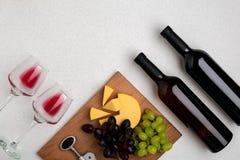 Dos vidrios de vino rojo, de queso y de uvas Visión superior Fotografía de archivo