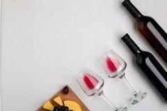 Dos vidrios de vino rojo, de queso y de uvas Visión superior Foto de archivo libre de regalías