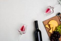 Dos vidrios de vino rojo, de queso y de uvas Visión superior Imagenes de archivo