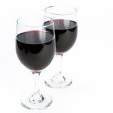 Dos vidrios de vino rojo en el aislamiento del fondo Fotografía de archivo libre de regalías