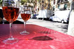 Dos vidrios de vino rojo en la tabla de un café de la calle en un día soleado brillante Fotografía de archivo libre de regalías
