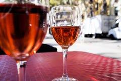 Dos vidrios de vino rojo en la tabla de un café de la calle en un día soleado brillante Foto de archivo libre de regalías