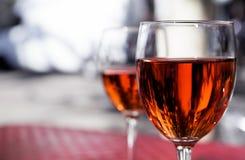 Dos vidrios de vino rojo en la tabla de un café de la calle en un día soleado brillante Fotos de archivo